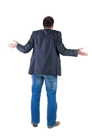 Back view of shocked and scared young business man. Holds hands upwards. Rear view. Isolated over white background. photo