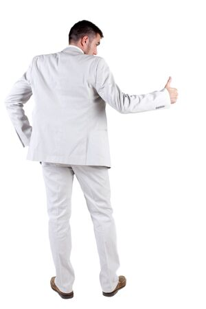 Back view of young business man in white suit going thumb up, isolated on white background. Rear view.Showing of positive emotions with OK sign concept . photo