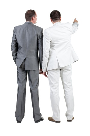 Back view of two businessman pointing at wall. rear view. Isolated over white .  Stock Photo