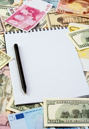 Opened spiral notepad (notebook) sheet in a cage on money background ( euro and dollars cash). with black pen photo