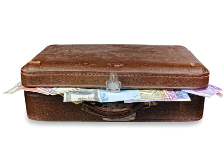 corporate greed: old suitcase full of money. shabby brown retro suitcase with world currencies