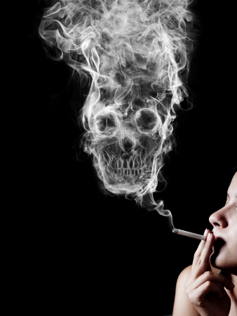 woman smoking a cigarette. Of smoke formed skull dead, as a symbol of the dangers of smoking to health and imminent death of people.  photo