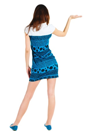 Back view of Beautiful woman in blue dress looking at wall and Holds a hand up. young brunette girl standing. Rear view people. Isolated over white background. Stock Photo - 13148236
