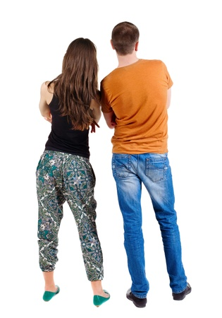 man side view: Back view of young couple (man and woman) hug and look into the distance. beautiful friendly girl and guy together. Rear view. Isolated over white background. The guy in the orange T-shirt and jeans, girl in green pants and a black T-shirt