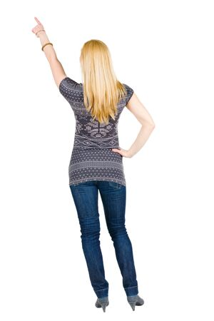 Back view of young brunette woman pointing at wall . beautiful girl in blue jeans and sweater showing gesture. Rear view. Isolated over white background. photo