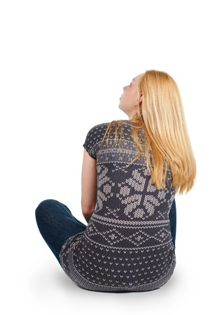Back view of beautiful young woman sitting on the floor and looks into the distance. Blonde girl relaxes. Rear view people. Isolated over white background. photo