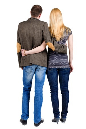 Back view of young couple (man and woman) hug and look into the distance. beautiful friendly girl and guy together. Rear view. Isolated over white background. man in a costume jacket, a woman in a sweater and jeans photo