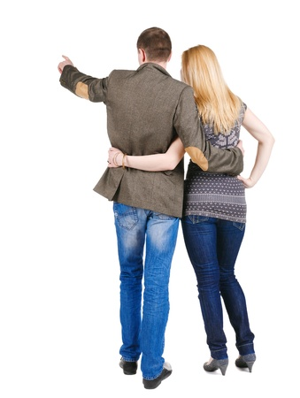 Back view of young couple pointing at wall.  Rear view. Isolated over white background. photo