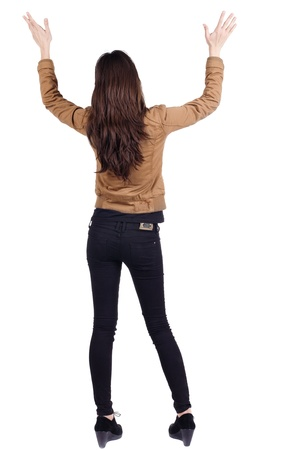 back posing: back view of surprised brunette woman with hands up. Girl in jacket. Rear view. Isolated over white  Stock Photo