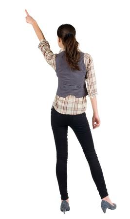 Vista trasera de una mujer joven morena señalando. hermosa chica en el gesto camisa. Aislado sobre fondo blanco. Vista trasera.