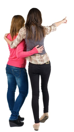 Back view of two young woman (brunette and blonde) pointing at wall . Rear view people collection.  backside view of person. beautiful girl friends  showing gesture. Isolated over white background.   photo