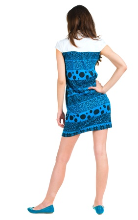 shot from behind: back view of standing beautiful brunette woman. Young girl in blue dress looking ahead of yoursel. Rear view people collection.  backside view of person. Isolated over white background.