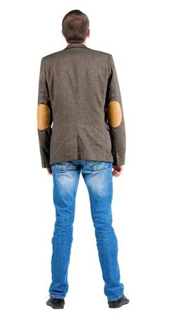 Vista posteriore di uomo d'affari in giacca alzare lo sguardo. In piedi ragazzo in jeans e giacca. Posteriore collezione vista le persone. vista posteriore della persona. Isolato su sfondo bianco.