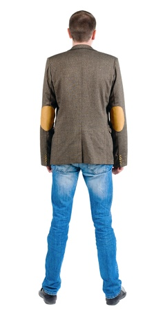 Back view of young business man in jacket  looking ahead of yourself.   Standing  handsome guy in jeans and suit jacket. Rear view people collection.  backside view of person. Isolated over white background. photo