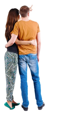 Back view of young couple pointing at wall. guy in the jeans and orange T-shirt and the girl in a fashion pants. looking into the distance. Rear view. Isolated over white background. photo