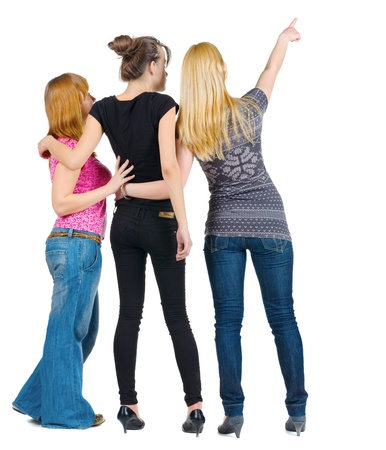 Back view of group beautiful women pointing at wall. Girl friends looks into the distance. Rear view people collection.  backside view of person. photo