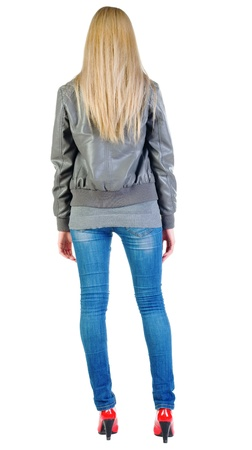 blue grey coat: back view of standing beautiful blonde woman. Young girl in jacket, jeans and red kitten heels. Rear view. Isolated over white background