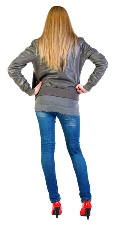 back view of standing beautiful blonde woman looks into  distance. Young girl in jacket, jeans and red kitten heels. backside view of person.  Rear view people collection.  Isolated over white background Stock Photo - 13355861