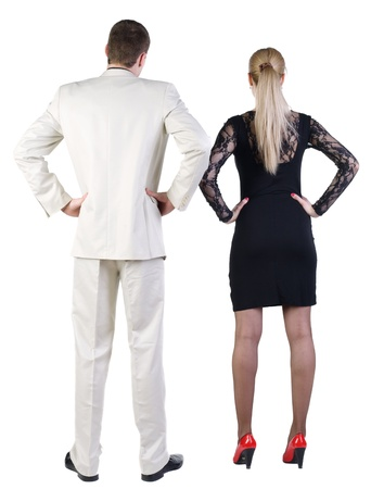 Back view of  business team look into the distance. young couple (man and woman) rear view.  beautiful friendly girl in dress and guy in suit together. Rear view. Isolated over white background.  photo