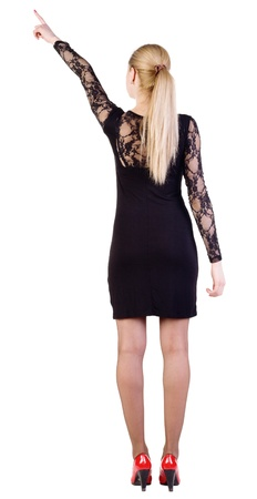 backside: Back view of young blonde woman pointing at wall . beautiful girl in dark dress and red kitten heels. Back view of young brunette woman pointing at wall . beautiful girl in blue dress showing gesture. Rear view. Isolated over white background.showing gest Stock Photo