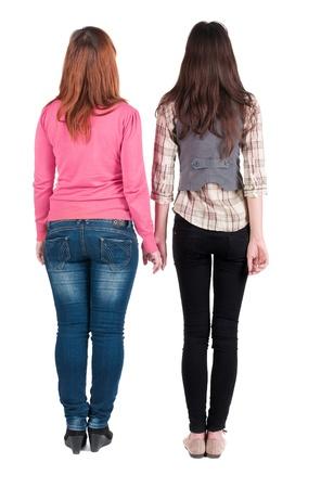 Zurück von zwei jungen Mädchen (brünett und blond) zu sehen. Rückansicht Menschen Kollektion. Rückansicht der Person. schöne Frau Freunden zeigen Geste. Rückansicht. Isolierte über weißem Hintergrund.