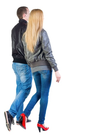 Back view of going young couple (man and woman) . walking beautiful friendly girl and guy in jacket and jeans together. Rear view people collection.  backside view of person.  Isolated over white background. Stock Photo