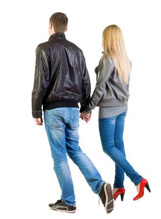 parejas caminando: pareja que j�venes (hombre y mujer) Vista trasera. caminar hermosa chica amable y hombre en la chaqueta y los pantalones vaqueros juntos. Vista posterior recogida de las personas. trasero vista de la persona. Aislado sobre fondo blanco.