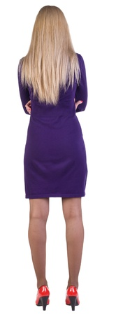 back view of standing beautiful business woman. Young blonde girl in violet dress and red kitten heels. Rear view. Isolated over white background.