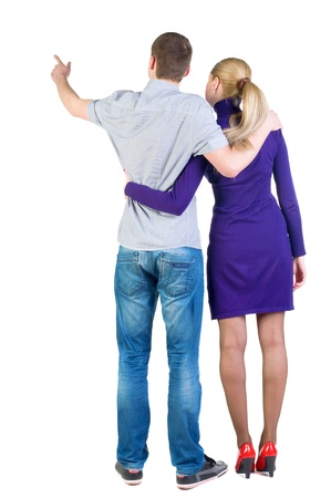young couple pointing at wal Back view  (woman and man). guy in the jeans shirt and  girl in blue dress looking into the distance. Rear view people collection.  backside view of person.  Isolated over white background. photo