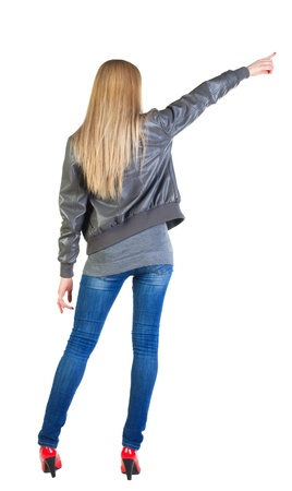 Back view of young blonde woman pointing at wall . beautiful girl in jeans, gray jacket and red kitten heels showing gesture. Rear view people collection.  backside view of person.  Isolated over white background. photo