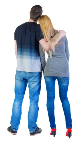 Back view of young couple (man and woman) hug and look into the distance. beautiful friendly girl and guy in shirt and jeans together. Rear view people collection.  backside view of person.  Isolated over white background. photo