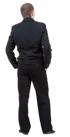 backside: back view of adult man in black suit  watching.   Businessman looks ahead.  Isolated over white background.