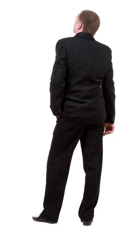 espalda: Vista trasera del hombre de negocios mira hacia adelante. Chico joven en traje negro observando. Aislado sobre fondo blanco. Vista posterior recogida de las personas. trasero vista de la persona. Foto de archivo