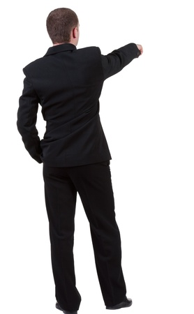 Back view of pointing business man. gesticulating young guy in black suit. Rear view people collection.  Isolated over white background.  backside view of person.  photo
