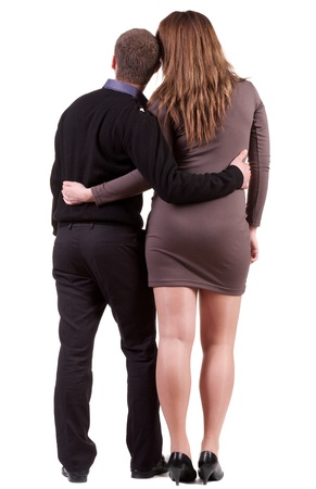 Back view of young embracing couple (man and woman) hug and look into the distance.  photo