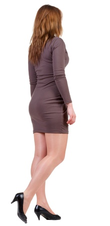 back view of going brunette woman  in brown dress. beautiful girl in motion.  backside view of person. Isolated over white background. Rear view people collection.  photo