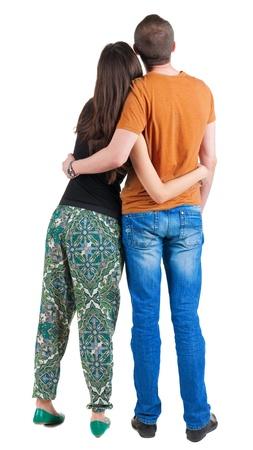 mujeres de espalda: Vista trasera de la joven pareja (hombre y mujer) un abrazo y mira en la distancia. hermosa chica y un chico agradable juntos. Vista posterior recogida de las personas. trasero vista de la persona. Aislado sobre fondo blanco. Foto de archivo