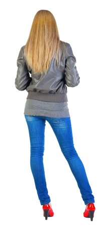back view of standing beautiful blonde Young woman.  girl in jacket, jeans and red kitten heels. Stock Photo - 13664066