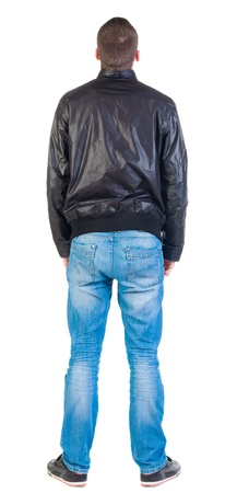 man rear view: Back view of handsome man in jacket  looking up.   Standing young guy in jeans and  jacket.