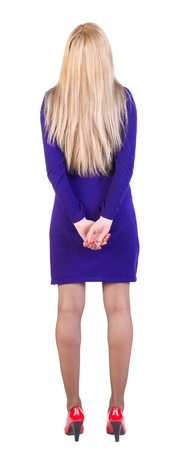 back view of standing beautiful blonde business woman. Young girl in violet dress and red kitten heels. Rear view people collection.  backside view of person.  Isolated over white background. photo