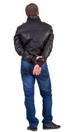 Back view of handsome man in jacket  looking up.   Standing young guy in jeans and  jacket.  photo