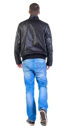 行き: ジャケットのハンサムな男を歩いての背面図です。ジーンズやジャケットの若い男です。背面ビューの人々 のコレクションです。人の裏面の表示します。白い背景の上に孤立しました。