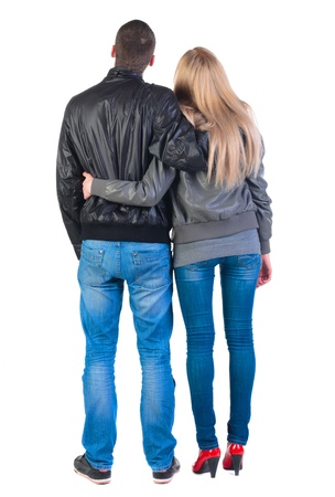 Back view of young couple (man and woman) hug and look into the distance. beautiful friendly girl and guy in jacket and jeans together. Rear view. Isolated over white background.  photo