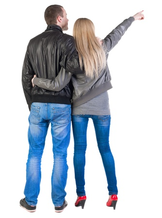 young couple pointing at wal Back view  (woman and man). guy in the jeans shirt and  girl in blue dress looking into the distance. Rear view people collection.  backside view of person.  Isolated over white background.