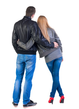 back  view: Back view of young couple (man and woman) hug and look into the distance. beautiful friendly girl and guy in jacket and jeans together. Rear view. Isolated over white background.