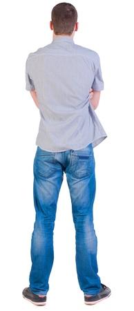 Achteraanzicht van jonge mannen in overhemd en jeans. Guy kijkt weg. Achteraanzicht mensen collectie. achterzijde uitzicht persoon. Geà ¯ soleerd op witte achtergrond.