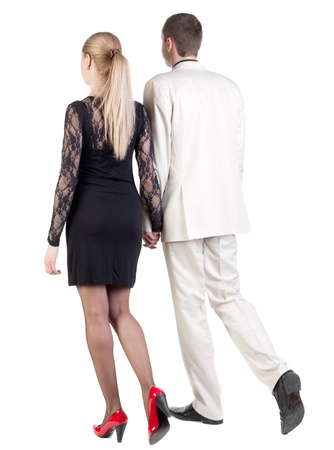 striding: Back view of going young business couple (man and woman) . walking beautiful friendly girl in dress and guy in suit. Rear view people collection.  backside view of person.  Isolated over white background.