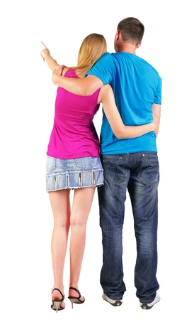Back view of young couple pointing at wall (woman and man). guy in the jeans and blue T-shirt and the girl in dress. looking into the distance. Rear view people collection.   backside view of person.  Isolated over white background. Imagens