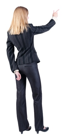 Back view of young blonde business woman pointing at wall . beautiful girl in dark suit. Rear view people collection. backside view of person.  Isolated over white background. photo
