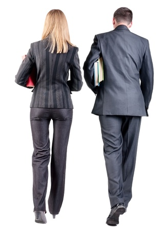 looking behind: Back view of  walking business team. Going young couple (man and woman) with books.  beautiful friendly girl and guy in suit together. Rear view people collection.  backside view of person.  Isolated over white background. Stock Photo